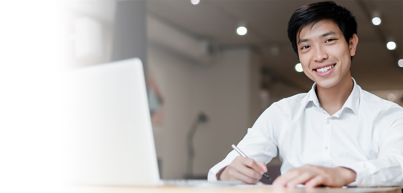 asian millennial businessman with laptop works at desk with documents